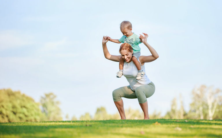 Young fitness woman working out outdoors while hoding son on shoulders