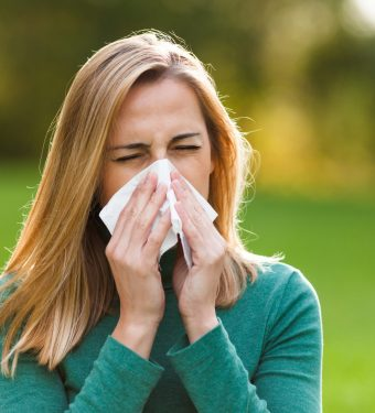 Young woman with allergy symptom blowing nose in park